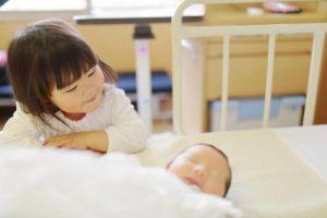 赤ちゃんを見る女の子の写真